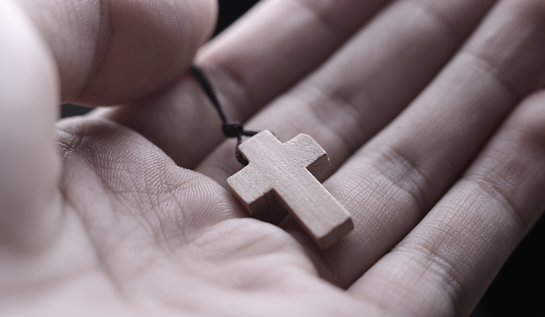 hand holding small wooden cross